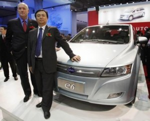 BYD President Wang Chuanfu, standing next to one of his electric cars